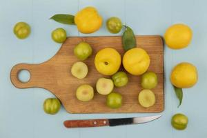 Top view of fresh green cherry plums and peaches on a blue background