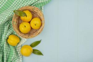 Top view of fresh yellow peaches on a bucket on a blue background with copy space