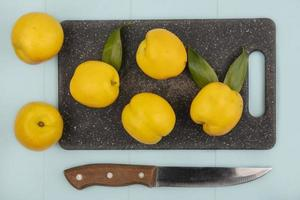 Top view of fresh yellow peaches on a kitchen cutting board with knife on a blue background