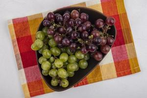 Top view of grapes in bowl on plaid cloth on white background