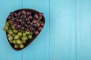 Top view of grapes in bowl on blue background with copy space