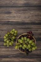 Vista superior de las uvas en la canasta y sobre fondo de madera con espacio de copia