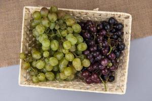 Vista superior de las uvas en la cesta de cilicio sobre fondo gris
