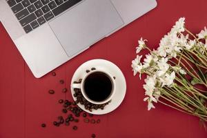Vista superior de café con flores blancas cerca de una computadora portátil