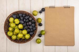 Vista superior de fruta fresca junto a un bloc de notas en blanco