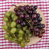 Top view of grapes on cutting board on plaid cloth background