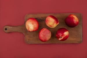 Vista superior de melocotones frescos y deliciosos aislado en una placa de cocina de madera sobre un fondo rojo.