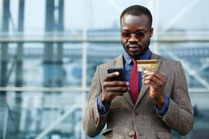 Stylish black businessman typing information from his credit card photo