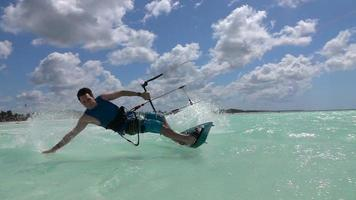 SLOW MOTION CLOSEUP: Cheerful surfer smiling and kiteboarding in tropical lagoon video