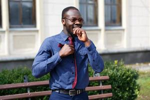 Handsome African American man fixes his red tie on blue shirt photo