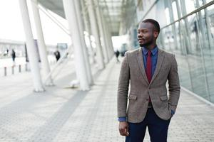 Stylish African American black businessman poses in a suit
