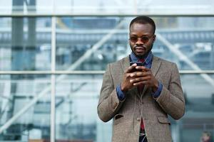 Stylish African American black businessman works on his smartphone