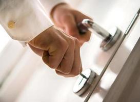 Hands inserting keys in door lock photo