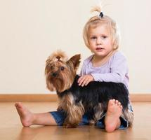 Cute little girl with yorkshire terrier indoor photo