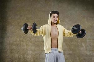 Young man training with dumbbells at indoor photo