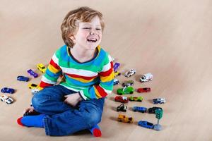 Funny little kid playing with lots of toy cars indoor.