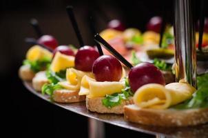 Banquete a la placa fourchette con canapés fondo oscuro tiro interior foto