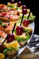 banquet a-la fourchette plate with canapes dark background indoor shot photo