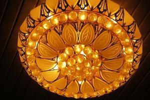 Hermosa araña de iluminación interior en el techo con fondo de textura foto