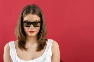 beautiful girl playing 3D video game isolated on red background