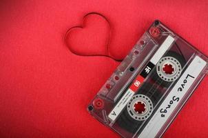 Casete de audio vintage con cinta suelta formando un corazón foto