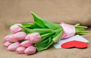 Bouquet of pink tulips with satin ribbon, envelope and heart photo