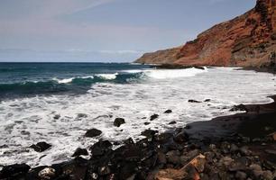 Waves crashing under red cliff