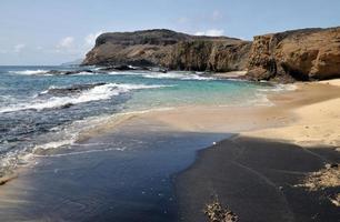 White, Black sand beach by the cliff
