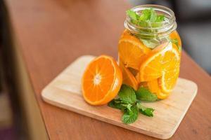 Mug delicious refreshing drink of orange fruit with mint