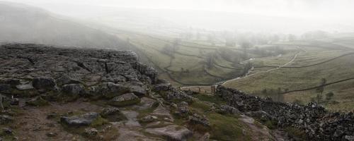 Panorama landscape foggy Autumnal view over limestone crag to va photo