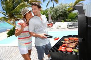 Cheerful couple preparing grilled meat for lunch near swimming-pool photo