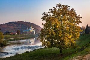 Monastery and tree near river in hazy autumn