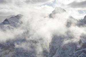 clouds hover over the mountain peaks photo