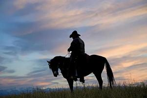 Cowboy silhouette against dawn sky.(see others in my portfolio/lightbox) photo
