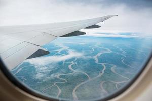view from airplane to the ground dotted with rivers