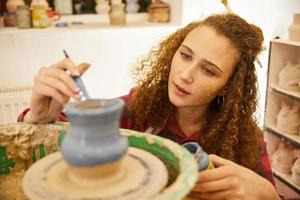 Girl painting pottery