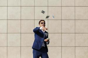 joven empresario tira dólares y baila en la calle