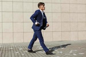joven empresario caminando a través de billetes de un dólar en la calle