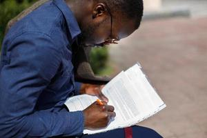 African American man signs papers sitting on the bench outside