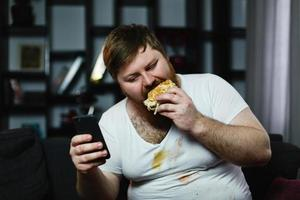 Man checks something in his smartphone while he eats a burger