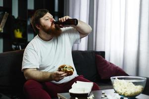 Fat man eats burger with beer sitting at the table