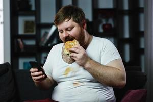 Fat man checks something in his smartphone while he eats a burger