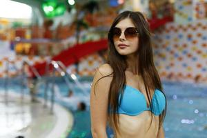 The girl stands near swimming pool