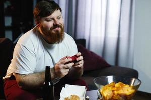 Happy fat man in dirty shirt plays video games