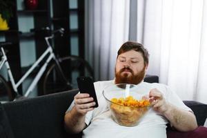 Pretty fat man smiles checking his smartphone