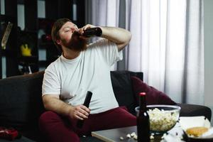 Fat man drinks beer lying on the sofa