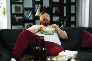 Happy fat man eats pop-corn lying on the sofa before a table with beer