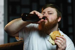 Fat man watches TV, eats burger and drinks beer