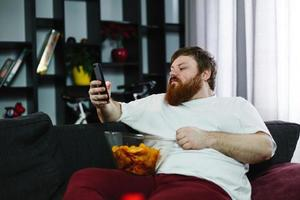 Man sitting on the sofa and eating chips