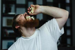 Close-up of a fat man looking ugly while he eats pop-corn